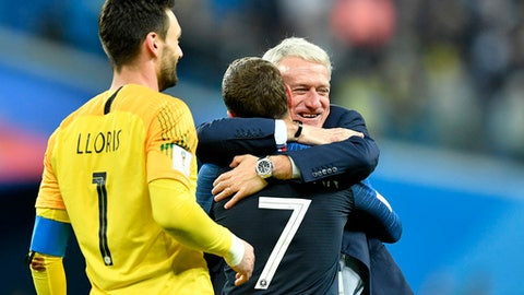 France head coach Didier Deschamps, right, hugs Antoine Griezmann after their team advanced to the final after the semifinal match between France and Belgium at the 2018 soccer World Cup in the St. Petersburg Stadium in St. Petersburg, Russia, Tuesday, July 10, 2018. (AP Photo/Martin Meissner)
