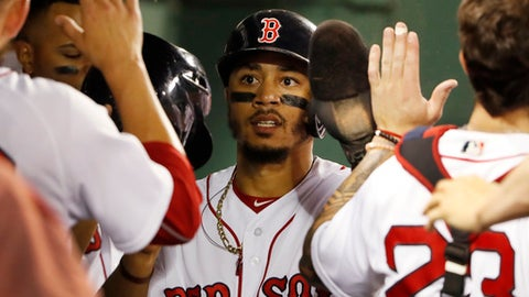 Boston Red Sox's Mookie Betts is congratulated in the dugout after scoring a run against the Texas Rangers during the seventh inning of a baseball game Tuesday, July 10, 2018, in Boston. (AP Photo/Winslow Townson)