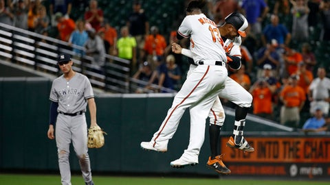 Baltimore Orioles' Jonathan Schoop, right, and Manny Machado celebrate in front of New York Yankees first baseman Greg Bird after Schoop hit a game-winning single in the ninth inning of a baseball game, Tuesday, July 10, 2018, in Baltimore. Caleb Joseph scored on the play, and Baltimore won 6-5. (AP Photo/Patrick Semansky)