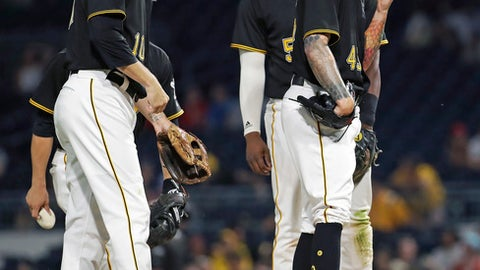 Pittsburgh Pirates relief pitcher Steven Brault, right, is joined by Jordy Mercer, left, and Josh Bell as he they wait for manager Clint Hurdle to change pitchers after Brault issued two bases-loaded walks in the sixth inning of a baseball game against the Washington Nationals in Pittsburgh, Tuesday, July 10, 2018. (AP Photo/Gene J. Puskar)