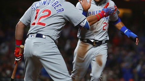 Chicago Cubs' Addison Russell, right, is congratulated by Kyle Schwarber after scoring on a wild pitch, and throwing error by San Francisco Giants catcher Nick Hundley during the seventh inning of a baseball game Tuesday, July 10, 2018, in San Francisco. (AP Photo/Ben Margot)