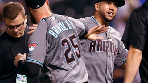 Arizona Diamondbacks relief pitcher Archie Bradley, left, congratulates right fielder David Peralta after the team's 5-3 win in a baseball game against the Colorado Rockies on Tuesday, July 10, 2018, in Denver. (AP Photo/David Zalubowski)