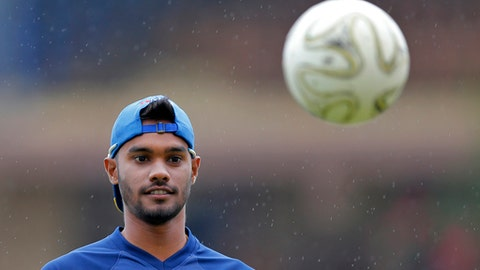 Sri Lanka's Sri Lanka's Dhananjaya de Silva looks at a soccer ball after their  practice session is disrupted due to rain ahead of the first test cricket match against South Africa in Galle, Sri Lanka, Wednesday, July 11, 2018. Sri Lanka will play a two match test series with touring South Africa starting from Thursday. (AP Photo/Eranga Jayawardena)