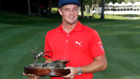 FILE - In this July 16, 2017, file photo, Bryson DeChambeau celebrates with the trophy after winning the John Deere Classic golf tournament, at TPC Deere Run in Silvis, Ill. DeChambeau will defend a title for the first time in his career this week at the John Deere Classic. (AP Photo/Charlie Neibergall, File)