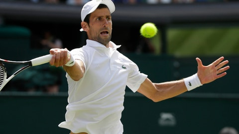 Novak Djokovic of Serbia returns the ball to Kei Nishikori of Japan during their men's quarterfinal match at the Wimbledon Tennis Championships in London Wednesday