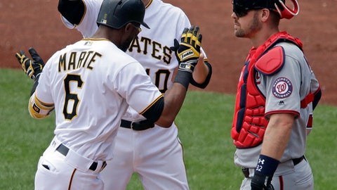 Washington Nationals catcher Matt Wieters, left, waits as Pittsburgh Pirates' Starling Marte (6) celebrates with Jordy Mercer after hitting a two-run home run off Nationals starting pitcher Gio Gonzalez in the third inning of a baseball game in Pittsburgh, Wednesday, July 11, 2018. (AP Photo/Gene J. Puskar)