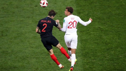 Croatia's Sime Vrsaljko jumps for the ball with England's Dele Alli, right, during the semifinal match between Croatia and England at the 2018 soccer World Cup in the Luzhniki Stadium in Moscow, Russia, Wednesday, July 11, 2018. (AP Photo/Thanassis Stavrakis)