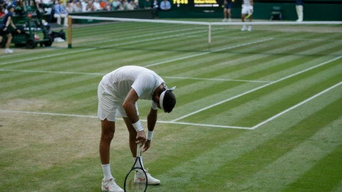 Juan Martin Del Potro of Argentina stands after falling on the court during the men's quarterfinal match against Rafael Nadal of Spain at the Wimbledon Tennis Championships in London, Wednesday July 11, 2018. (AP Photo/Tim Ireland)