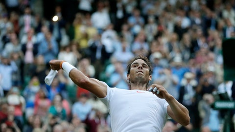 Rafael Nadal of Spain throws his wrist bands into the crowd after defeating Juan Martin Del Potro of Argentina in their men's quarterfinal match at the Wimbledon Tennis Championships in London, Wednesday July 11, 2018. (AP Photo/Kirsty Wigglesworth)