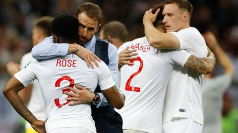 England head coach Gareth Southgate, 2nd left, comforts England's Danny Rose, left, after loosing the semifinal match between Croatia and England at the 2018 soccer World Cup in the Luzhniki Stadium in Moscow, Russia, Wednesday, July 11, 2018. (AP Photo/Francisco Seco)