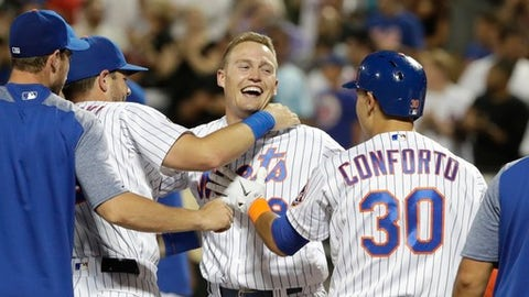 New York Mets' Brandon Nimmo (9) celebrates with teammates Kevin Plawecki and Michael Conforto (30) after hitting a walk-off three-run home run during the 10th inning of a baseball game against the Philadelphia Phillies on Wednesday, July 11, 2018, in New York. The Mets won 3-0. (AP Photo/Frank Franklin II)