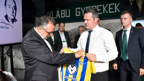"""President of the Federation of Jewish Religious Communities of Hungary Andras Heisler, left, is presented with a club jersey by General Manager of the Israeli soccer club Maccabi Tel Aviv Ben Mansford, as President of the Hungarian soccer club FTC Gabor Kubatov, right, looks on,  during a joint commemoration of Mazsihisz and the soccer club Ferencvarosi Torna Club, about Istvan """"Potya"""" Toth in the club's museum in Budapest, Hungary, Thursday, July 12, 2018.  Istvan""""Potya"""" Toth was arrested by Gestapo and executed by Hitler's Hungarian nazi allies during the German occupation of Hungary in February 1945. FTC plays the soccer Europe League first qualifying round first leg match against Maccabi Tel Aviv later Thursday. (Tibor Illyes/MTI via AP)"""