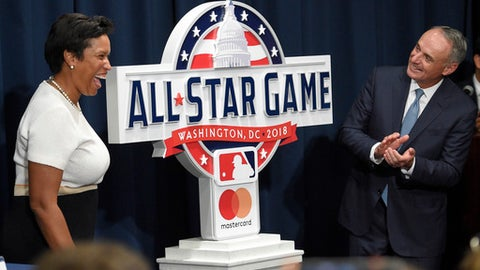 FILE - In this July 26, 2017, file photo, Muriel Bowser, left, Mayor of the District of Columbia, and Rob Manfred, Commissioner of Baseball, react at a baseball press conference to unveil the 2018 MLB All-Star Game logo, in Washington. Thirteen years after Major League Baseball returned to Washington and almost that long since Mark and father Ted Lerner were chosen as owners of their new hometown team, they finally get to throw their party. The fourth All-Star Game in the nations capital and first since 1969 is a celebration of a new generation of Washingtonians rediscovering the connection to baseball that for so long wasnt a part of the towns sporting identity.(AP Photo/Nick Wass, File)
