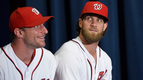 FILE - In this July 26, 2017, file photo, Washington Nationals' Max Scherzer, left, and Bryce Harper look on at a baseball press conference to unveil the 2018 MLB All-Star Game logo, in Washington. Thirteen years after Major League Baseball returned to Washington and almost that long since Mark and father Ted Lerner were chosen as owners of their new hometown team, they finally get to throw their party. The fourth All-Star Game in the nations capital and first since 1969 is a celebration of a new generation of Washingtonians rediscovering the connection to baseball that for so long wasnt a part of the towns sporting identity. (AP Photo/Nick Wass, File)