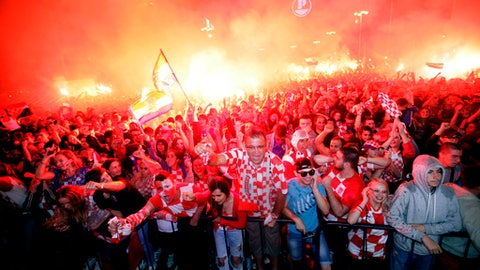 FILE - In this July 11, 2018 file photo, Croatian fans cheer while watching the semifinal match between Croatia and England at the 2018 soccer World Cup, in Zagreb, Croatia. In the Balkans, even soccer is political, so it is no surprise that Croatia's stunning success at the World Cup creates mixed reactions and strong emotions in the region scarred by war. (AP Photo/Nikola Solic, File)