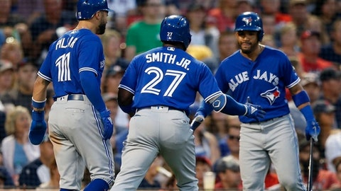 Toronto Blue Jays' Dwight Smith Jr. (27) celebrates his two-run home run that also drove in Kevin Pillar (11) during the third inning of a baseball game against the Boston Red Sox in Boston, Friday, July 13, 2018. (AP Photo/Michael Dwyer)
