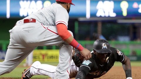 Miami Marlins' Cameron Maybin is picked off at first base as Philadelphia Phillies first baseman Carlos Santana makes the tag during the third inning of a baseball game Friday, July 13, 2018, in Miami. (AP Photo/Lynne Sladky)