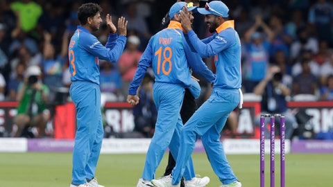 India's Kuldeep Yadav, left, celebrates taking the wicket of England captain Eoin Morgan during the one day cricket match between England and India at Lord's cricket ground in London, Saturday, July 14, 2018. (AP Photo/Matt Dunham)