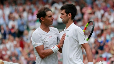 Novak Djokovic of Serbia, right, meets Rafael Nadal of Spain at the net after defeating him in the men's singles semifinal match at the Wimbledon Tennis Championships, in London, Saturday July 14, 2018. (Andrew Couldridge, Pool via AP)