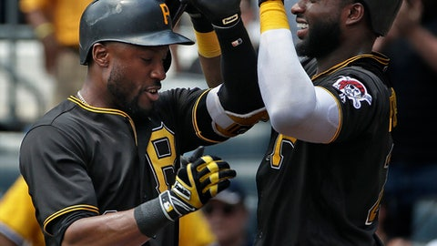 Pittsburgh Pirates' Starling Marte, left, is greeted by Gregory Polanco as he returns to the dugout after hitting a solo home run off Milwaukee Brewers starting pitcher Chase Anderson  in the first inning of a baseball game in Pittsburgh, Saturday, July 14, 2018. Polanco also hit a home run in his following at-bat.. (AP Photo/Gene J. Puskar)