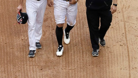 Chicago White Sox second baseman Yoan Moncada, center, leaves with a team trainer and bench coach Joe McEwing, left, after an injury in the fifth inning of a baseball game against the Kansas City Royals, Saturday, July 14, 2018, in Chicago. (AP Photo/Nam Y. Huh)