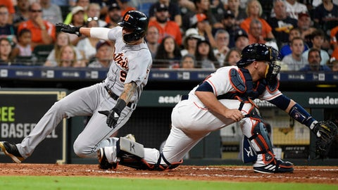 Detroit Tigers' Nicholas Castellanos, left, scores a run on James McCann's RBI-double past Houston Astros catcher Tim Federowicz during the sixth inning of a baseball game, Saturday, July 14, 2018, in Houston. (AP Photo/Eric Christian Smith)