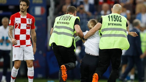 Security stewards remove people who ran onto the pitch and briefly stopped the final match between France and Croatia at the 2018 soccer World Cup in the Luzhniki Stadium in Moscow, Russia, Sunday, July 15, 2018. (AP Photo/Francisco Seco)