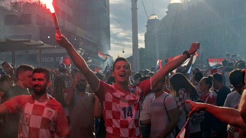 A supporter of the Croatian national soccer team lights a flare in central Zagreb, Croatia, Sunday, July 15, 2018. Croatia's national soccer team lost to France in the World Cup final in Russia. (AP Photo/Marko Drobnjakovic)