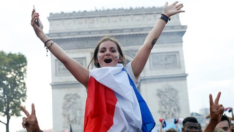 French soccer fans react on the Champs Elysees avenue with the Arc de Triomphe on background, after defeated Croatia in the final match at the 2018 soccer World Cup, in Paris, France, Sunday, July 15, 2018. France won the final 4-2. (AP Photo/Thibault Camus)