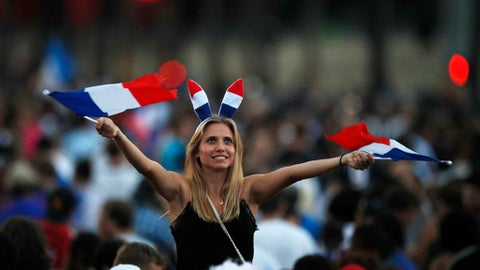 A woman waves French flag on the Champs Elysees avenue after France won the soccer World Cup final match between France and Croatia, Sunday, July 15, 2018 in Paris. France won its second World Cup title by beating Croatia 4-2 . (AP Photo/Francois Mori)