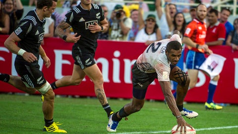 FILE - In this Saturday, Dec. 5, 2015 file photo, Jasa Veremalua of Fiji scores as Lewis Ormond and Declan O'Donnell of New Zealand chase in the Cup Semi Final of the Sevens World Series rugby tournament in Dubai, United Arab Emirates. A new format for the Rugby World Cup Sevens starting on Friday, July 20, 2018 in San Francisco has dumped pool play and gone straight to knockout rounds, seemingly to appeal to the short attention span of American sports fans. World Rugby calls the change exciting and innovative. Others see the immediate pressure as brutal. (AP Photo/Stephen Hindley, file)