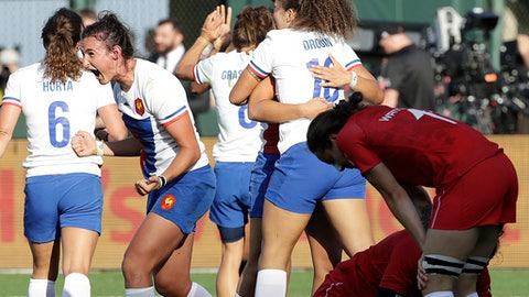 France's Shannon Izar, second from left, and teammates celebrate as Canada players react to a France score during the Women's Rugby Sevens World Cup in San Francisco, Friday, July 20, 2018. (AP Photo/Jeff Chiu)