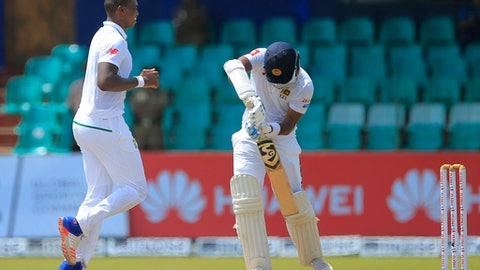 South Africa's Lungi Ngidi, left, celebrates the dismissal of Sri Lanka's Dimuth Karunaratne, right, during the third days play of their second test cricket match in Colombo, Sri Lanka, Sunday, July 22, 2018. (AP Photo/Eranga Jayawardena)