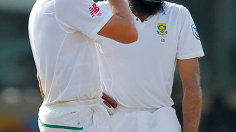 South Africa's Theunis de Bruyn, wipes his face as Hashim Amla awaits a third umpire decision during the day three of their second test cricket match with Sri Lanka in Colombo, Sri Lanka, Sunday, July 22, 2018. (AP Photo/Eranga Jayawardena)