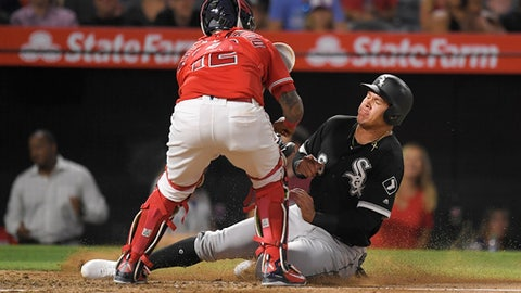 Chicago White Sox's Avisail Garcia is tagged out at home by Los Angeles Angels catcher Martin Maldonado as he tries to score on a fielder's choice by Matt Davidson during the sixth inning of a baseball game Tuesday, July 24, 2018, in Anaheim, Calif. (AP Photo/Mark J. Terrill)