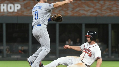 Los Angeles Dodgers second baseman Logan Forsythe throws out Atlanta Braves' Nick Markakis at first base after forcing out Charlie Culberson, right, at second base during the eighth inning of a baseball game Saturday, July 28, 2018, in Atlanta. (AP Photo/John Amis)