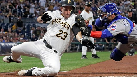 Chicago Cubs catcher Willson Contreras, right, tags out Pittsburgh Pirates' David Freese, who was attempting to score from second on a single by Francisco Cervelli off Cubs starting pitcher Jon Lester during the fifth inning of a baseball game in Pittsburgh, Tuesday, July 31, 2018. (AP Photo/Gene J. Puskar)