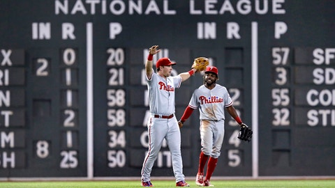 Philadelphia Phillies left fielder Rhys Hoskins, left, and center fielder Roman Quinn, right, celebrate after defeating the Boston Red Sox 3-1 in a baseball game at Fenway Park in Boston, Tuesday, July 31, 2018. (AP Photo/Charles Krupa)