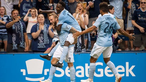 Jul 7, 2018; Kansas City, KS, USA; Sporting Kansas City forward Gerso Fernandes (12) and Sporting Kansas City defender Jaylin Lindsey (26) celebrate with Sporting Kansas City forward Johnny Russell (7) after he scores a goal in the second half against Toronto FC at Children's Mercy Park. Mandatory Credit: Amy Kontras-USA TODAY Sports