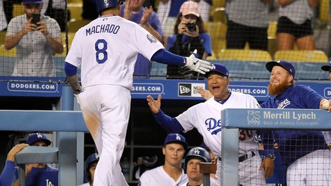 Los Angeles Dodgers' Manny Machado, left, is congratulated by manager Dave Roberts, center, and Justin Turner after hitting a solo home run during the ninth inning of a baseball game against the Milwaukee Brewers, Monday, July 30, 2018, in Los Angeles. Milwaukee won 5-2. (AP Photo/Mark J. Terrill)