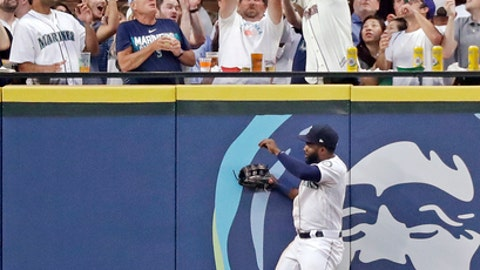 Seattle Mariners left fielder Denard Span comes down from a leap at the wall as fans behind reach for the home run of Houston Astros' Evan Gattis during the sixth inning of a baseball game Tuesday, July 31, 2018, in Seattle. (AP Photo/Elaine Thompson)