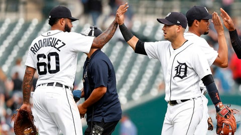 Detroit Tigers' Ronny Rodriguez (60) and Jose Iglesias celebrate their 7-4 win against the Cincinnati Reds after a baseball game in Detroit, Wednesday, Aug. 1, 2018. (AP Photo/Paul Sancya)