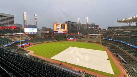 A tarp covers the infield during a delay before a baseball game between the Miami Marlins and the Atlanta Braves, Wednesday, Aug. 1, 2018, in Atlanta. (AP Photo/Todd Kirkland)