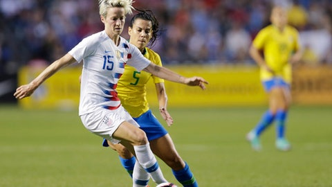 U.S. forward Megan Rapinoe works with the ball in front of Brazil midfielder Thaisa during the fist half of a Tournament of Nations soccer match Thursday, Aug. 2, 2018, in Bridgeview, Ill. (AP Photo/Annie Rice)