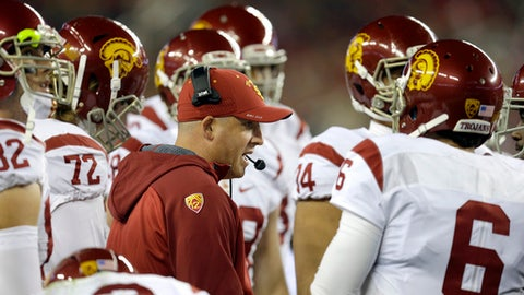 FILE - In this Dec. 5, 2015, file photo, Southern California interim coach Clay Helton, center, speaks with quarterback Cody Kessler (6) during the first quarter of the Pac-12 Conference championship NCAA college football game against Stanford in Santa Clara, Calif. Helton took the interim role in 2015 following Steve Sarkisian's in-season dismissal. Helton's 5-2 run as a fill-in got him hired as the full-time head coach. He has gone 21-6 the past two seasons, and the Trojans won the Pac-12 title last season. Helton was rewarded in February with a contract extension through 2023. (AP Photo/Ben Margot, File)