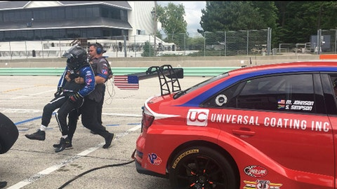 Sports car driver Michael Johnson is carried from his car during a driver change while testing at Road America in Elkhart Lake, Wis., Thursday, Aug. 2, 2018. Johnson won 14 national motorcycle championships by age 12 and was on the cusp of landing a deal for a permanent ride with a manufacturer when his budding career skidded to a dramatic halt on a dirt track in Sarnia, Ontario, Canada in 2005. He was involved in a crash, suffering a broken collarbone, broken left ankle, broken left leg, broken ribs and, worst of all, two fractured vertebrae in his back, which caused the paralysis. The first thing out of his mouth, he said, Dont make me quit racing, said his father, Tim, a former motorcycle racer.  (AP Photo/Genaro C. Armas)