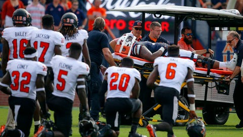 FILE - In this Saturday, Sept. 16, 2017 file photo, Mercer players watch as Auburn offensive lineman Darius James (78) is carted off after an injury during the first half of an NCAA college football game in Auburn, Ala. Darius James was pretty sure he was OK, even though he couldn't turn his neck. He wiggled his fingers and toes and had feeling in his arms and legs, giving the big offensive lineman some reassurance that he wasn't paralyzed. But his neck wouldn't budge. (AP Photo/Butch Dill, File)