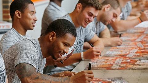 <p>               Oklahoma State wide receiver Tyron Johnson, front, signs an autograph as he sits with teammates Jalen McCleskey, left, and Dillon Stoner, right, during the NCAA college football team's fan appreciation day in Stillwater, Okla., Saturday, Aug. 4, 2018. (AP Photo/Sue Ogrocki)             </p>