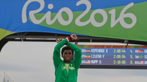"<p>               FILE - In this file photo dated Sunday, Aug. 21, 2016, Silver medal Ethiopia's Feyisa Lilesa, crosses his arms as he celebrates on the podium after the men's marathon at the 2016 Summer Olympics in Rio de Janeiro, Brazil.  Lilesa went into exile after protesting against oppression in his home country while winning a silver medal at the 2016 Rio Olympics, but according to an open letter published Wednesday Aug. 15, 2018, from Ethiopian Athletics Federation and the country's Olympic committee, he has been asked to return home to give him ""a hero's welcome.""(AP Photo/Luca Bruno, FILE)             </p>"