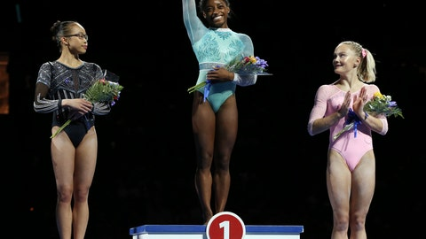 <p>               Top all-around finisher Simone Biles waves as second place Morgan Hurd and third place Riley McCusker look on at the U.S. Gymnastics Championships, Sunday, Aug. 19, 2018, in Boston. (AP Photo/Elise Amendola)             </p>